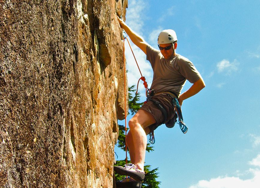man rock climbing wearing a helmet