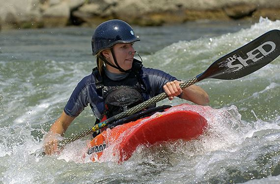 a women kayaking through rapids wearing a helmet