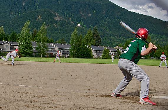 boys playing baseball with mountains in the background